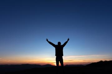 Victoire d'un homme au sommet d'une montagne au coucher de soleil