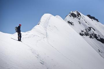 Bergsteiger steigt zum Gipfel über Firngrat.