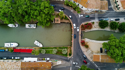 Aerial top view of boats and lock in Canal du Midi, road and bridge from above, Southern France