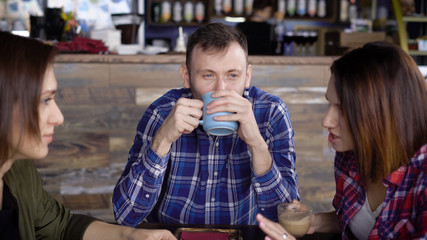 Interesting appearance, an adult man enjoys coffee, which is poured into a blue cup, not paying attention to the two girls who are chatting in the foreground