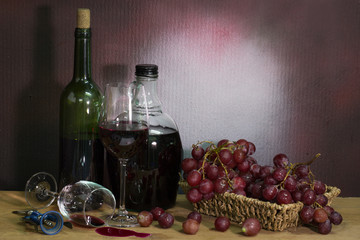 Bottle wine with wine glass and grape in basket  on the plank in dim light room