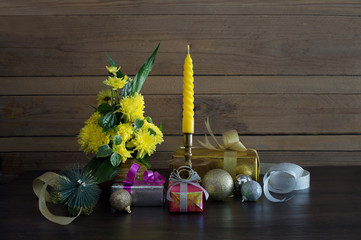 Gift and christmas ball and bouquet flower and yellow candle decoration for merry christmas and happy new year on dark background in dim light