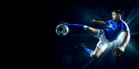 Soccer player performs an action play on a dark background. Player wears unbranded sport uniform.