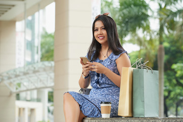 Beautiful Asian woman sitting on bench with shopping bags, holding  smartphone and smiling at camera