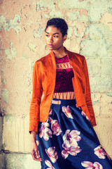 Portrait of Young African American Woman in New York, wearing fashionable orange red jacket, dark red under top, dark blue flower patterned skirt, standing by painted wall on street, looking away..