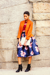 Unhappy Young African American Woman thinking outside in New York, wearing orange red jacket, flower patterned skirt, black boot shoes, holding laptop computer, standing by stone wall on campus, sad..