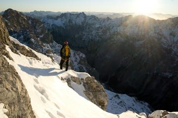 Bergsteiger klettert den Jubiläumsgrat im Winter bei Schnee von der Zugspitze zur Alpspitze bei Sonnenaufgang