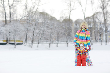 young woman and a young child in a bright colored clothing playing in the winter snow