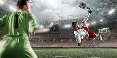 Soccer player scores the ball into the goal on professional stadium. The goalkeeper protects the football gate. Players wears unbranded sport uniform.