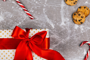 Present box with red ribbon lies on grey floor with Christmas cookies, gingerbreads and red white candies