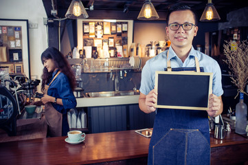 Portrait of smiling asian barista holding blank chalkboard menu in coffee shop. Cafe restaurant service, food and drink industry concept.