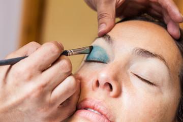 Make up artist applying eyeshadow to a woman