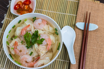 high-angle shot shrimp wonton noodle soup with, on a table set for lunch or dinner.