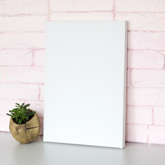 Mock up poster in interior. Blank canvas, pink brick wall on background.