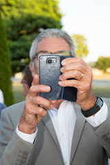 an old man take a selfie with smartphone or a picture of you