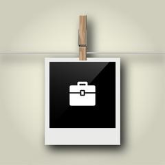 Sofortbild mit Symbol an Wäscheleine - Koffer