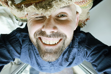 cheerful smiling man with a beard in a summer straw hat