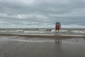 Lonely lifeguard stand holding firm against crashing waves