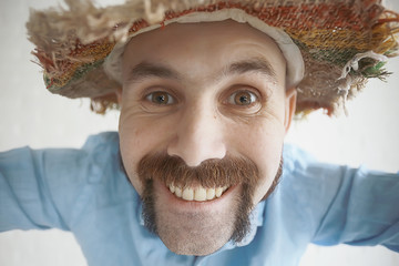 cheerful guy with a mustache in a straw hat