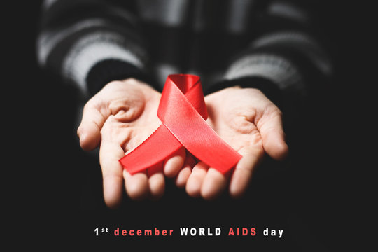 red aids ribbon in hand on black background and text 1st december world aids day