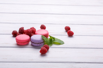 pink macaroons with raspberries and mint on white background