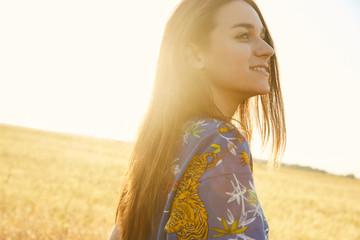 Portrait of a girl walking in the fields of wheat enjoying sunset
