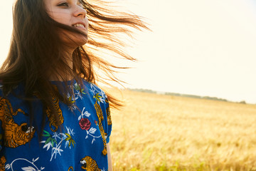 Portrait of a girl walking in the fields of wheat enjoying sunset with her hair waving
