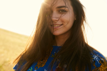 Portrait of a girl walking in the fields of wheat enjoying sunset with her hair waving on her face