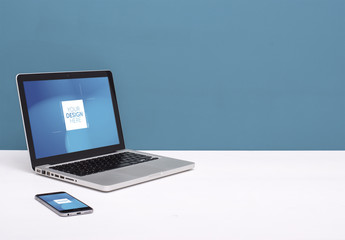Laptop and Smartphone on White Desk with Blue Background Mockup