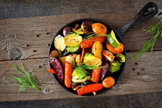 Cast iron skillet of roasted autumn vegetables against a rustic dark background
