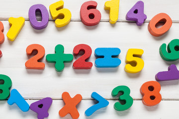 Multicolored numbers on a wooden background. View from above. For your design.