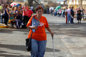 A woman walks from a government unemployment office as residents affected by Hurricane Maria wait in line to receive and register for unemployment benefits in the municipality of Guaynabo outside San Juan