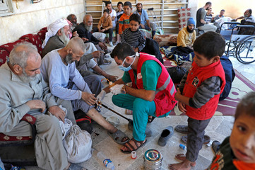 Medics treat civilians who got wounded at Raqqa's frontline at a mosque in Raqqa