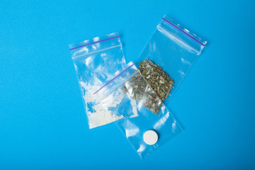 Three doses of drugs in plastic bags. Marijuana, white powder and tablets.