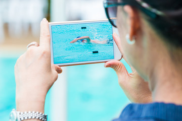 woman taking picture of her son swimming with her smart phone