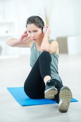 Woman exercising at home wearing headphones