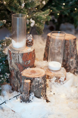 The composition of two decorative candles in glass on a snow-covered tree stump in the woods.