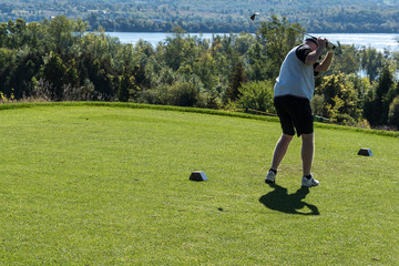Golfer in mid swing, lake and trees in background