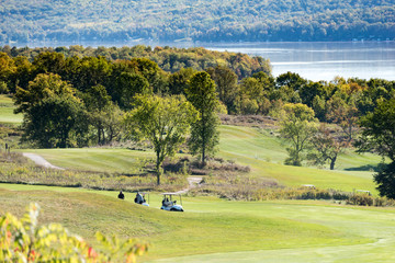 golfers and golf carts on hilly golf course