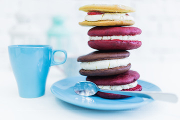 Stack of four whoopie pies or moon pies with cup and spoon.