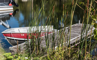 small red boat moored to wooden dock