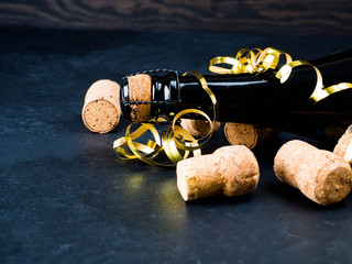 a bottle of champagne and a number of tubes, holiday concept, dark background