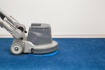 Blue carpet chemical cleaning with professionally disk machine. Early spring regular cleanup. Cleaning service concept.
