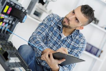 Male technician assessing photocopier