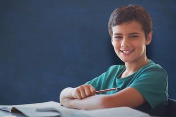 Composite image of portrait of boy doing homework