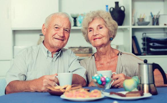 Happy mature couple drinking tea in kitchen