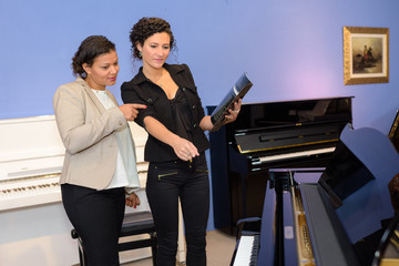 Women looking at pianos