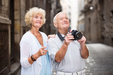 Romantic senior couple making photo of city