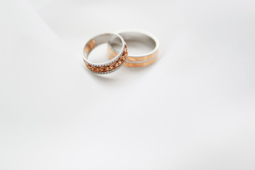Engagement two rings on a soft white background fabric. A wedding ring is a symbol of love and happiness.