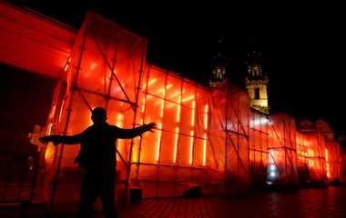 A man dances in front of an installation at the Old Town Square during a light festival in Prague